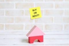 Selectieve nadruk van gele kleverige die nota's met BUY OF HUUR worden geschreven? met huisspeelgoed op witte houten achtergrond  stock foto