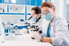 selectieve nadruk van wetenschappers in medische maskers en beschermende brillen die door microscopen op regenten kijken stock foto