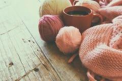 Selectieve nadrukfoto van roze comfortabele gebreide sjaal met aan kop koffie en wolgarenballen op een houten lijst Royalty-vrije Stock Afbeeldingen