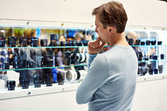 Selecting camera lens in showcase of store Stock Photos