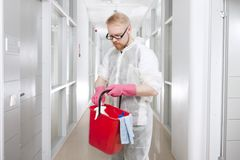 Selecting Detergents. Man in Overall Picking Cleanser from Red Bucket stock photos