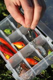 Selecting fishing lure. Fisherman selects fishing lure from lure box royalty free stock photos