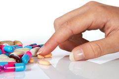 Selecting pills. Well manicured hand selecting all sorts of pills Stock Photo