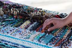 Selecting a Souvenir. A man reaches to pick up a beaded bracelet from a table of handmade jewelry at a beach market in Belize Royalty Free Stock Photography