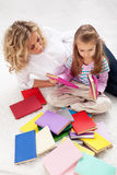 Selecting a story to read. Women and little girl with lots of books Royalty Free Stock Photo