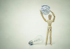 Selecting a stupid chioce. Wood Figure Mannequin carrying crumpled paper ball instead of an incandescent light bulb / Selecting a stupid chioce Stock Photography