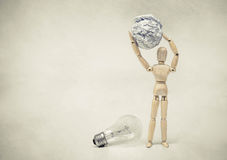 Selecting a stupid chioce. Wood Figure Mannequin carrying crumpled paper ball instead of an incandescent light bulb / Selecting a stupid chioce Royalty Free Stock Images