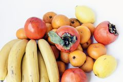 A selection of arranged different fresh fruits of bananas, mandarins, persimmons and lemons on white background close up stock photography