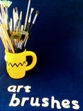 Selection of artists paint brushes. A wide selection of artists paint brushes in a bright yellow mug  set in a light and dark blue surround with wooden words Stock Images