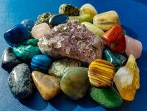 Selection of beautiful gem stones. Large pile of gem stones on blue background Stock Image