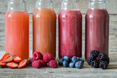 Selection of berry smoothies on rustic wood background Royalty Free Stock Images