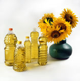 A selection of bottles of sunflower oil and a bouquet of sunflowers stock image