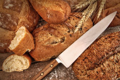 A selection of bread loaves with knife. On wood table royalty free stock photo