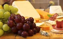 Selection of cheese and crackers with grapes Stock Images