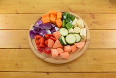 Selection of chopped vegetables on a wooden chopping board Royalty Free Stock Photos