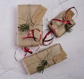 Selection of Christmas presents. With lables tied with string and red ribbon Royalty Free Stock Photo