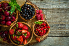 Selection of colorful berries on rustic background. Copy space Stock Photos