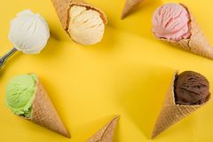 Selection of colorful ice cream scoops on yellow background. Top view royalty free stock images
