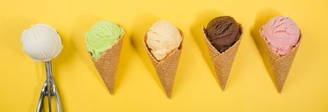 Selection of colorful ice cream scoops on yellow background royalty free stock photos