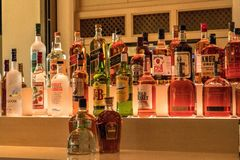 Selection of colorful liquor alcohol bottles line the shelf of a royalty free stock image
