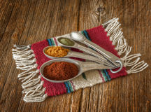 Selection of colorful spices in measuring spoons on an old worn Stock Photography
