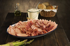 Selection of cured meat in a rustic setting. Country style selection of cured meat on rustic table Royalty Free Stock Photo
