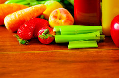Selection of delicious fruits and vegetables spread out on wooden surface, beautiful colors, healthy lifestyle concept Royalty Free Stock Images