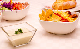 Selection of different delicious dishes sitting on white table, philly sandwich, tortilla salad Stock Photo