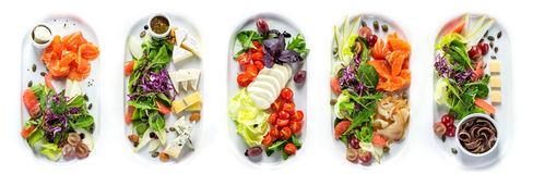 Selection of different kinds of cheese and fish. With greens and vegetables. Range of plates over white background stock photos