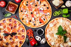 Selection of different pizzas on a black background and ingredients. Peperoni, Vegetarian and Seafood Pizza.  royalty free stock photos