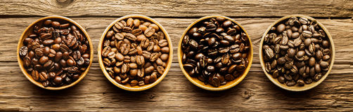 Selection of different roasted coffee beans. Selection of four different fresh dried roasted coffee beans in individual containers arranged in a line viewed from Stock Photos