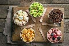 Selection of different rolled ice creams in cone cups. Rustic wood background, copy space royalty free stock photography
