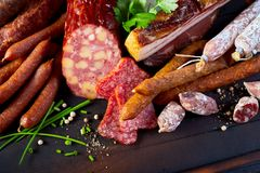 Selection of dried spicy sausages and fresh herbs. Selection of dried spicy pork and beef sausages, salami and bacon or ham with fresh herbs on a wooden table Stock Photography