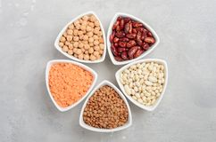 Selection of dry legumes, lentils and peas in white bowls on gray concrete background. Top view, flat lay, copy space Royalty Free Stock Photo