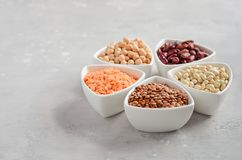 Selection of dry legumes, lentils and peas in white bowls on gray concrete background. Selective focus, copy space Stock Image