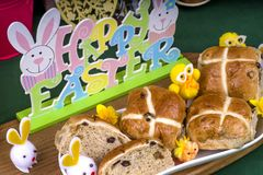 Easter Hot Cross Buns. Selection of Easter Hot Cross Buns with chocolate Easter Eggs and spring flowers with novelty chicks royalty free stock photo