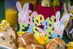 Easter Hot Cross Buns. Selection of Easter Hot Cross Buns with chocolate Easter Eggs and spring flowers with novelty chicks stock photos