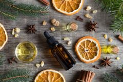 Selection of essential oils with Christmas spices and ingredient. S: bottles of essential oil, spruce, fir, frankincense resin, star anise, cinnamon, clove royalty free stock photos