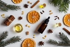Selection of essential oils with Christmas spices and ingredient. S on white background: bottles of essential oil, spruce, fir, frankincense resin, star anise royalty free stock photo