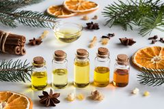 Selection of essential oils with Christmas spices on a white background. Christmas selection of essential oils and spices on white background: bottles of stock photography
