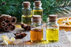 Selection of essential oils with star anise, cinnamon, frankincense and pine branches. Selection of essential oils with star anise, cinnamon, frankincense resin stock photos