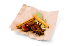 Selection of Exotic Spices on brown paper. Selection of Exotic Spices - cinnamon, cardamom, star anise, bay leaves and dried chillies - on brown paper Stock Photography