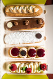 Selection of french pastry called eclairs. Glazed with chocolate, decorated with whipped cream, mascarpone, raspberries and coconut flakes Royalty Free Stock Image