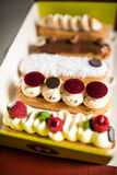 Selection of french pastry called eclairs. Glazed with chocolate, decorated with whipped cream, mascarpone, raspberries and coconut flakes Stock Photography