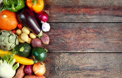 Selection of fresh autumn vegetables in a border. To the left side of the frame over a rustic wooden background with copyspace, overhead view Stock Photography