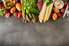 Selection of fresh fruit and veggies for asparagus. Selection of fresh fruit and veggies to accompany green and white spring asparagus spears arranged as a stock images