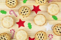 Selection of mince pies and christmas decorations. Selection of fresh golden brown mince pies and christmas decorations on a wooden background Stock Photography