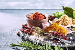 Selection of fresh herbs and spices for cooking. With rosemary, bay leaves, chili, curcuma, ginger, peppercorns and salt on a rustic tray with copy space stock photo
