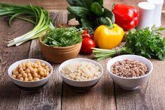 Selection of fresh vegetables and cooked cereal, grains and legume. Healthy plant based vegan food. Chickpeas, quinoa and buckwheat in bowls on rustic wooden stock image