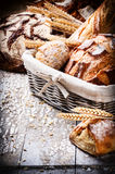 Selection of freshly baked bread in wicker basket Stock Photos